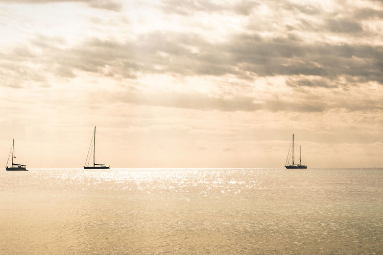 Sailboats sailing in sea against cloudy sky