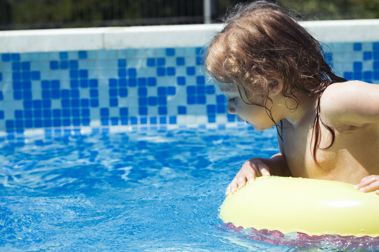 Curious toddler child safety in a swimming pool Children Copy Space Exploring Kids Swimming Blue Boys Child Childhood Day Kid Leisure Activity Lifestyles Little Little Girl Negative Space One Person Outdoors Poolside Real People Sunlight Swimming Swimming Pool Vacations Water