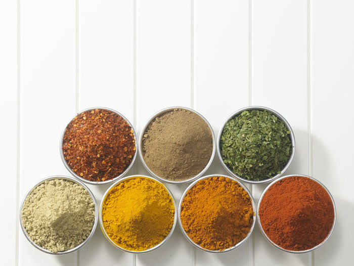 arrangement of spices on the white background Chili Pepper Copy Space Curry Assortment Cardamom Choice Cinnamon Condiment Cumin Directly Above Food Food And Drink Freshness Ground - Culinary Group Of Objects High Angle View Indian Food Ingredient No People Season  Spice Still Life Turmeric  Variation Variety