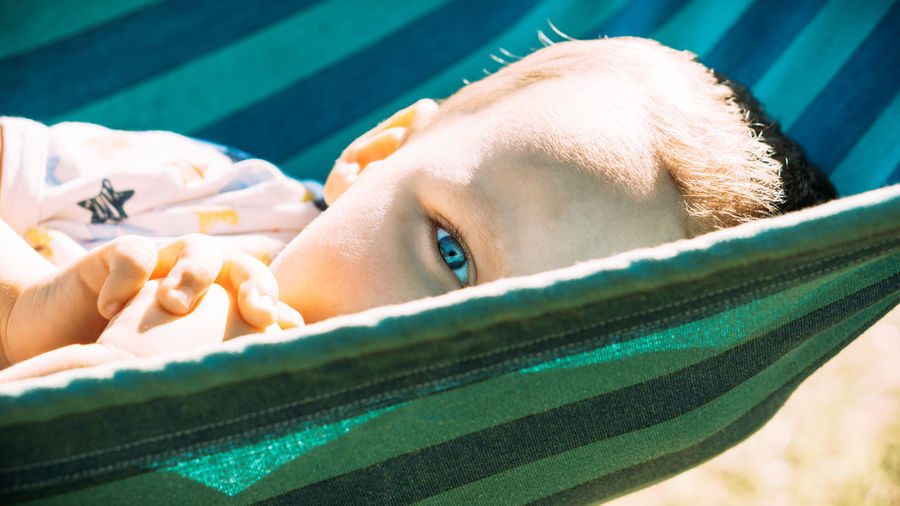 Close-up portrait of young woman lying on swimming pool