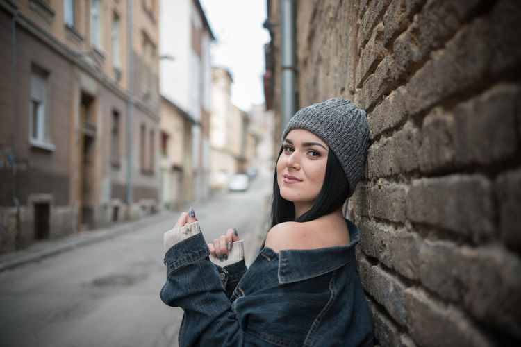 Side view portrait of young woman standing by brick wall in city