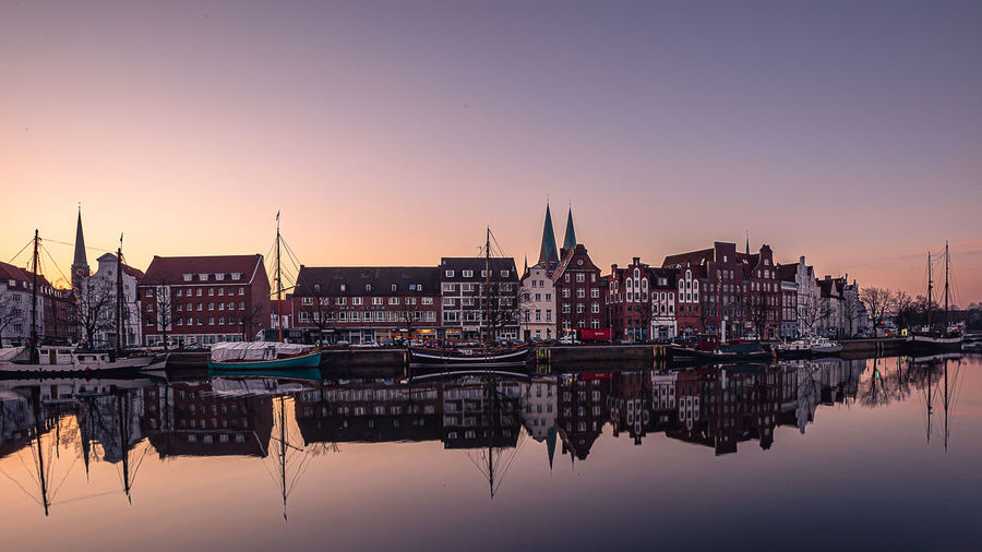 Sailboats in river by buildings against sky during sunset