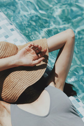 Low section of woman sitting by swimming pool