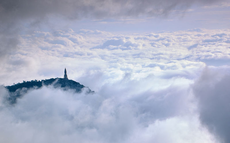 Aerial view of communications tower on hill against clouds