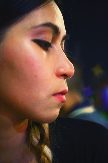 Close-up of woman looking down outdoors at night