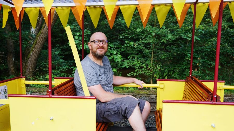 Portrait Of Smiling Bald Man Sitting In Park