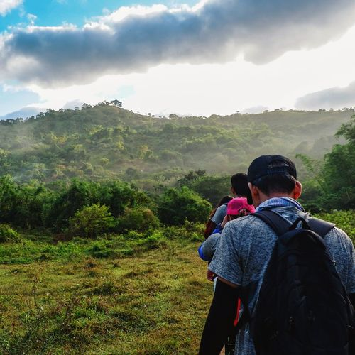 Rear View Of Man And Woman Hiking On Mountain