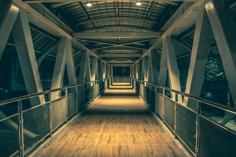 empty corridor in modern building Architecture Direction The Way Forward Built Structure Empty Indoors  No People Diminishing Perspective Railing Ceiling Building Absence Illuminated Bridge Connection Day Footpath Lighting Equipment Elevated Walkway Architecture Corridor