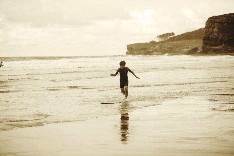 Boy running on beach against sky