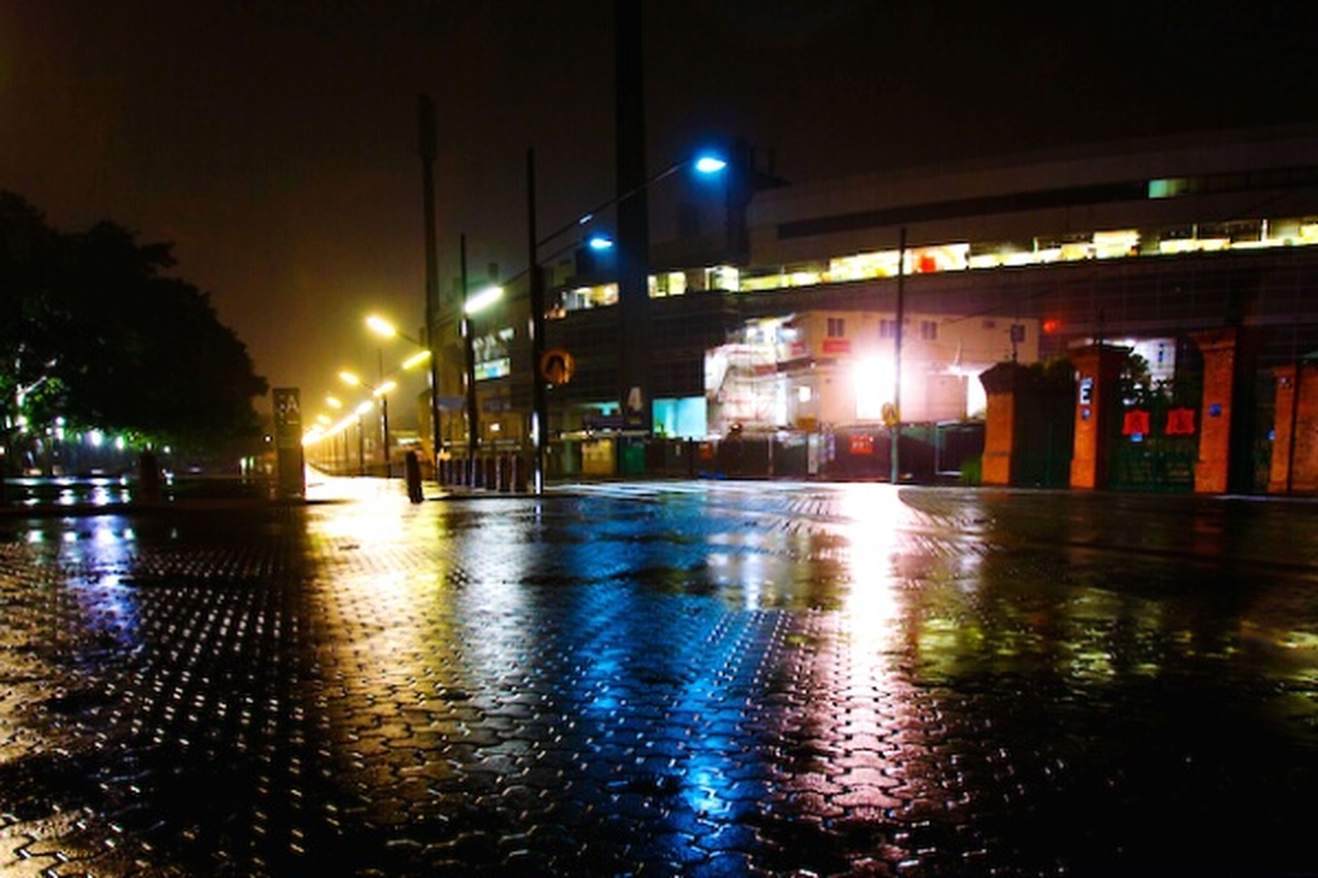 illuminated, night, building exterior, architecture, built structure, street light, reflection, city, street, lighting equipment, water, wet, sidewalk, building, incidental people, outdoors, light - natural phenomenon, city life, transportation, waterfront