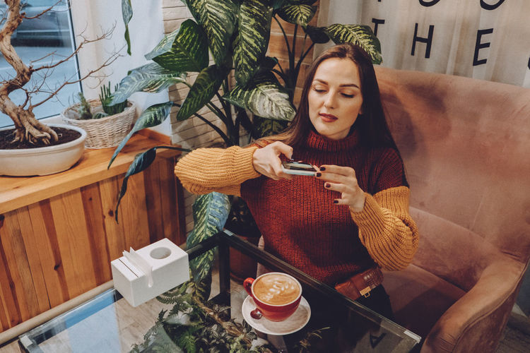 High angel view of woman sitting by coffee cup at home