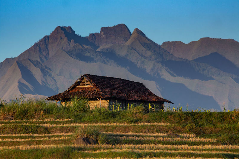 Old house on field by mountains against sky