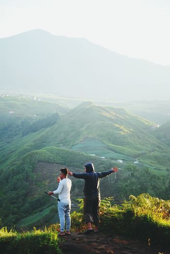Rear View Of Friends Standing On Mountain