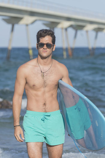 Young surfer posing with his surfboard seaside Alone Fun Lifestyle M Man Mediterranean  Millennial Pink Surfer Wafest Beach Board Coast Joy Outdoors People Portrait Sea Sport Summer Surface Level Surfboard Trendy Water Waves Wet This Is Masculinity