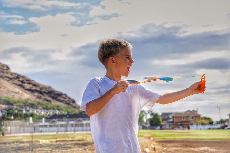 Boy playing with airplane on field against sky