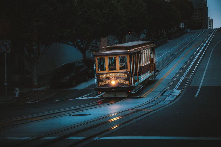 Illuminated railroad tracks by road at night