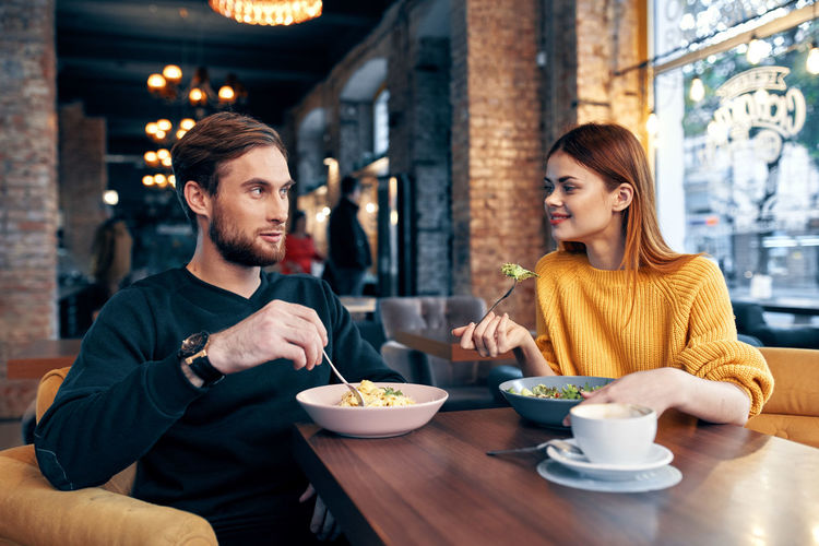 Young couple sitting on table at restaurant