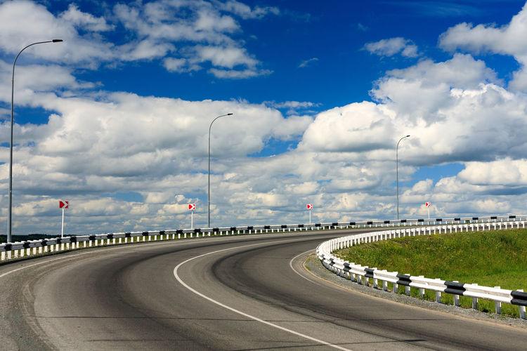 Asphalt Cloud - Sky Crash Barrier Curve Day Direction Dividing Line Highway Marking No People Outdoors Road Road Marking Sky Street Light