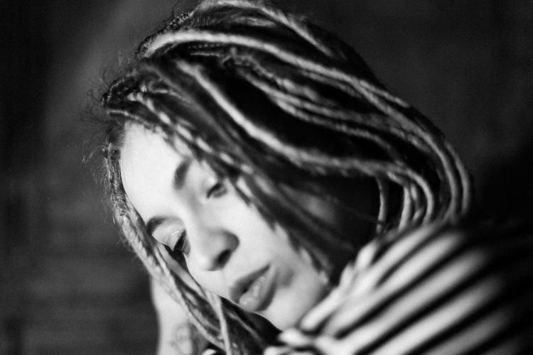 Close-up of young woman with dreadlocks looking away in dark