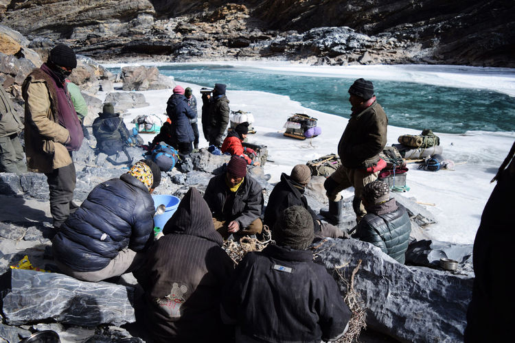 porters and trekkers resting after trekking on frozen Zanskar River Extreme Weather Winter Relaxing Resting Hiking Adventure Chadar Trek 2016 Day Escapism Frozen Nature Helper Ladakh Leisure Activity Lifestyles Men Mountain Outdoors Porter Real People Sitting Sledge Trekking Vacations Warm Clothing Rocky Mountains Backpack Hiker