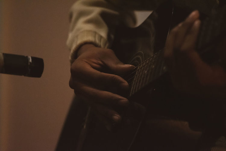 Cropped hands of person playing guitar