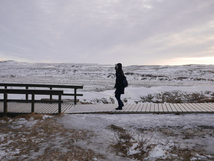 Woman Walking On Boardwalk Over Frozen Landscape Against Sky