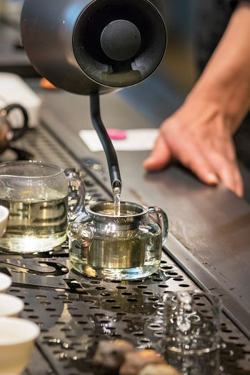 Close-up of person pouring hot water in glass tea cup.