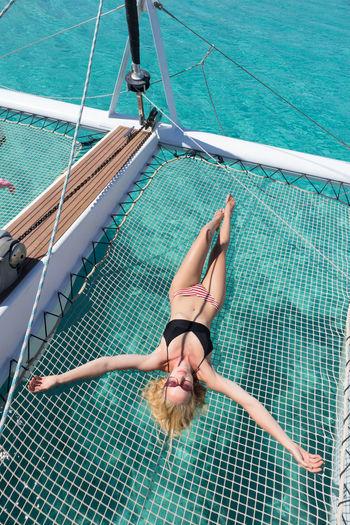 High angle view of woman lying on net over sea