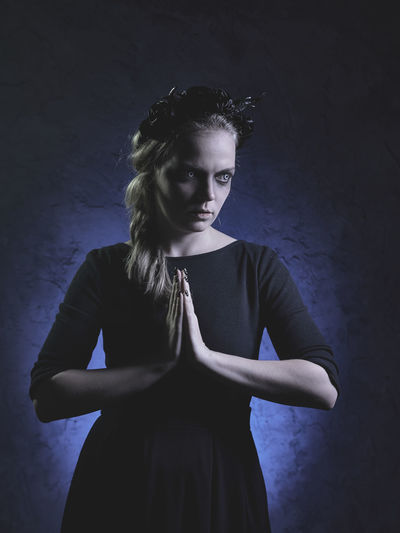 Spooky Woman In Prayer Position Standing Against Black Background