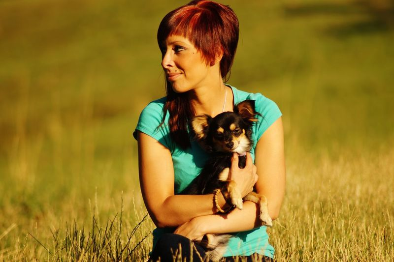 Smiling redhead woman carrying dog while sitting on grassy field