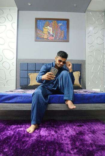 Man clicking selfie with smart phone while sitting on bed at home