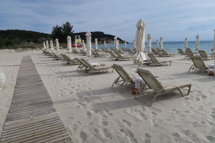 Lounge Chairs And Umbrella At Beach Against Sky