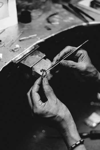 Cropped hands of jeweler making ring in workshop