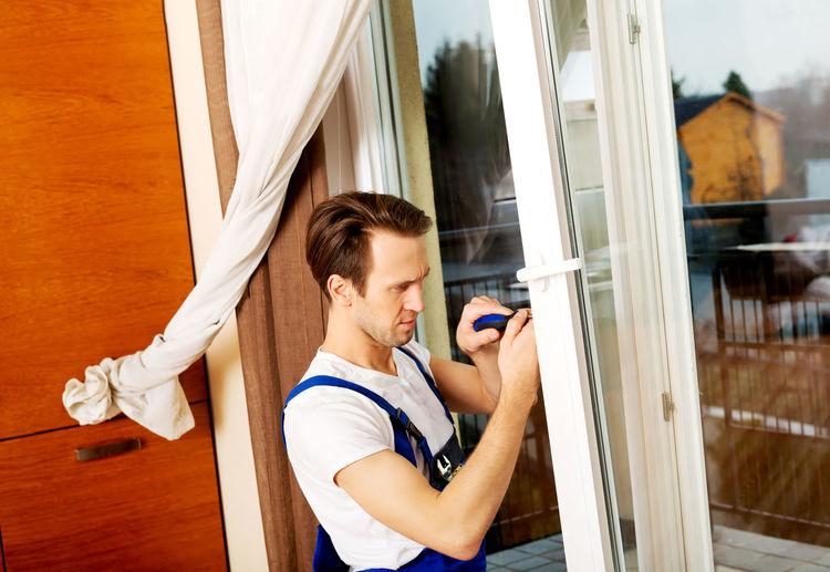 Man repairing sliding door at home