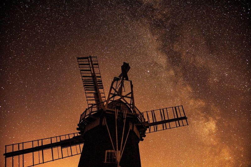 Low angle view of silhouette windmill against sky at night