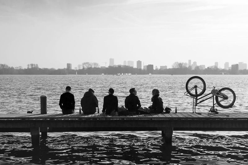 Rear View Of Friends Sitting On Pier On Sea Looking At City View