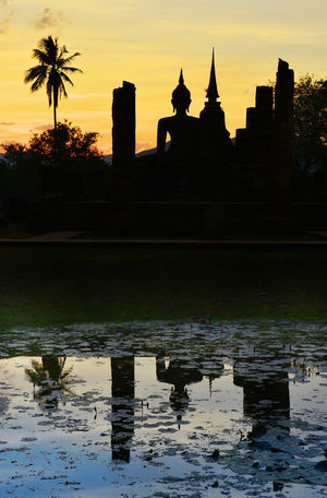 Buddha statue in sunset time. Sukhothai Historical Park, Sukhothai, Thailand. Sukhothai Historical Park Sukhothai, Thailand Ancient Ancient Civilization Architecture Building Exterior Built Structure Day History Nature Old Ruin Outdoors Place Of Worship Reflection Religion Sculpture Silhouette Sky Spirituality Statue Sukhothai Sunset Travel Travel Destinations Water
