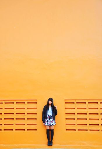 Full Length Of Woman Standing Against Orange Wall