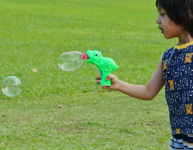 Kidsphotography Kids Playing Kids Being Kids Bubbles Bubble Gun Kids Children Only Child Childhood Bubble One Person Bubble Wand Outdoors Standing Grass Fun Day Side View