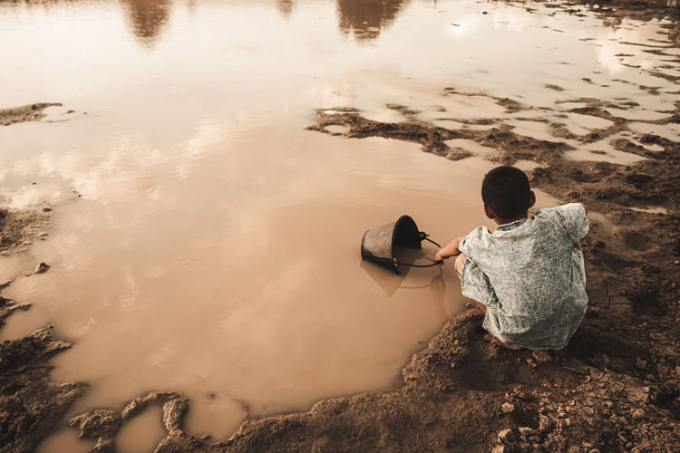 Rear view of boy collecting water from lake in bucket