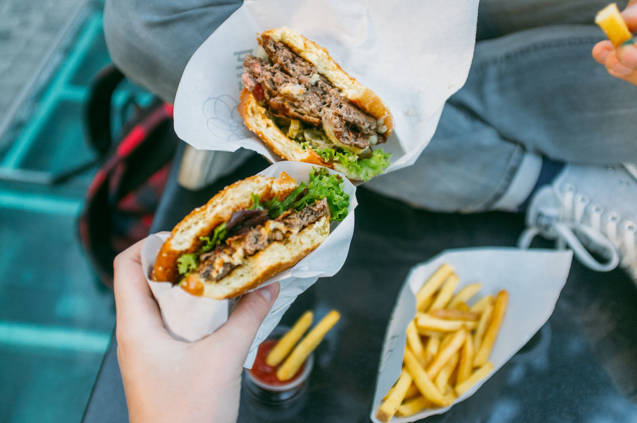 Cropped image of friends holding burger
