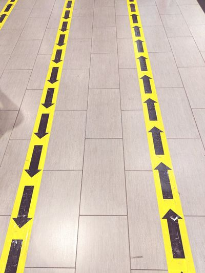 High angle view of arrow signs on tiled floor