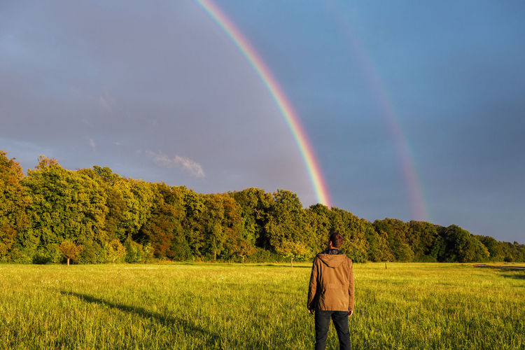 Rear view of man standing on field against rainbow in sky