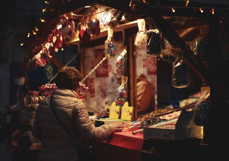Person standing in market at night during christmas