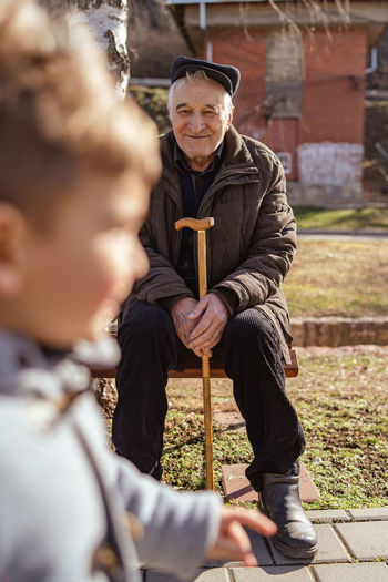 Senior man looking at grandson while sitting on bench in park