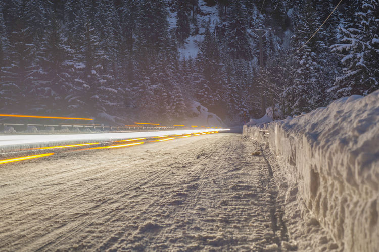 Light Trails On Snowy Road At Night During Winter