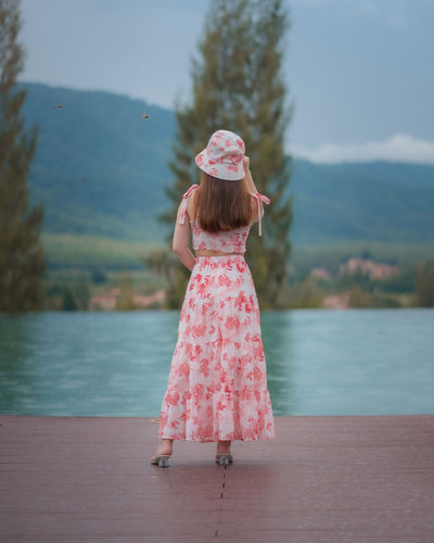 Rear view of girl standing on pink cloth