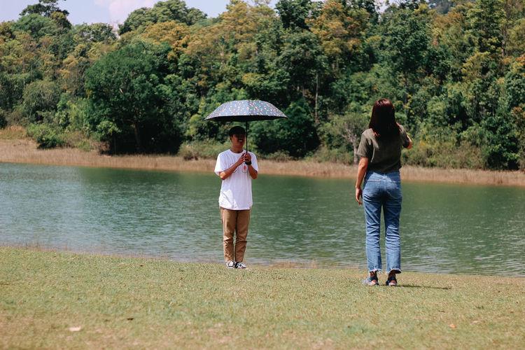Full length rear view of women on lake against trees
