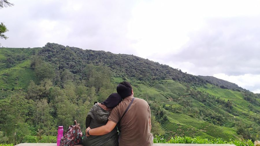 Rear view of couple on mountain against sky