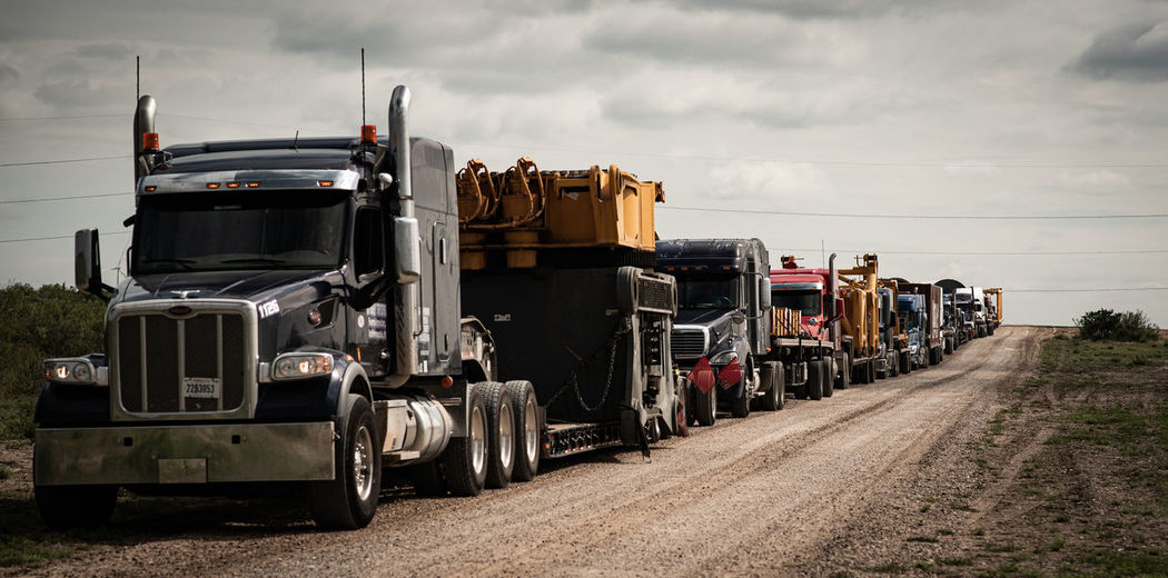 Stack of truck on road by field against sky